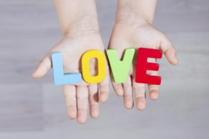 Hands holding the Word Love